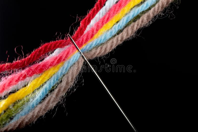 On a black background, several bright multicolored woolen threads are pass through the eye of the needle. Close-up.  royalty free stock photo