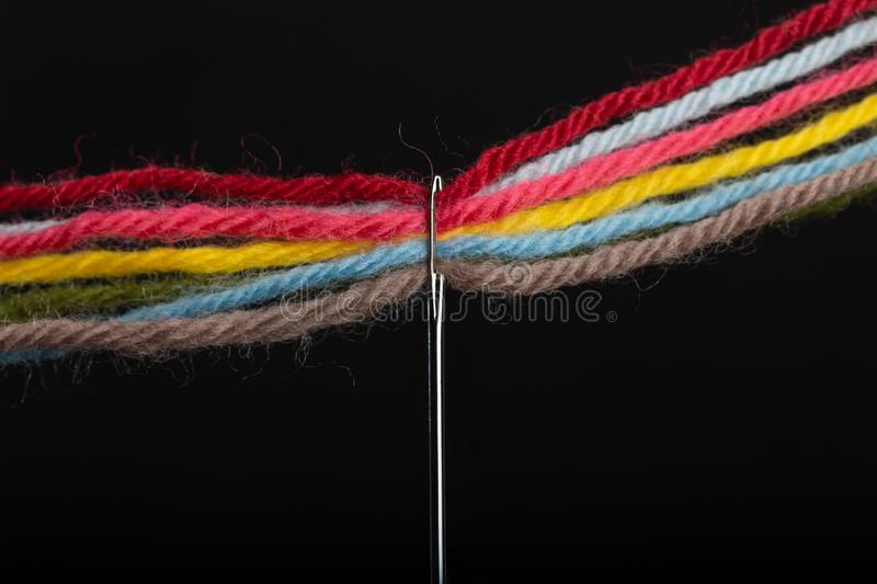 On a black background, several bright multicolored woolen threads are pass through the eye of the needle. Close-up stock photo