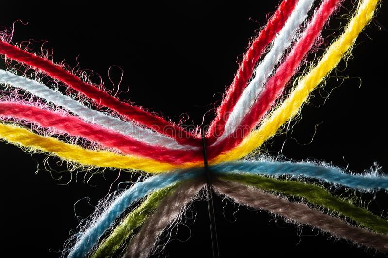 On a black background, several bright multicolored woolen threads are pass through the eye of the needle. Close-up. Backlight royalty free stock photography