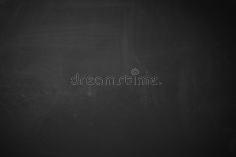 Black background showing matte rough wood blackboard texture with erased chalk. royalty free stock image