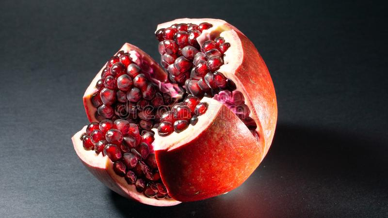 Black background, side view, in the middle of the photo an open pomegranate is seen. On which grains of fruit are visible royalty free stock images