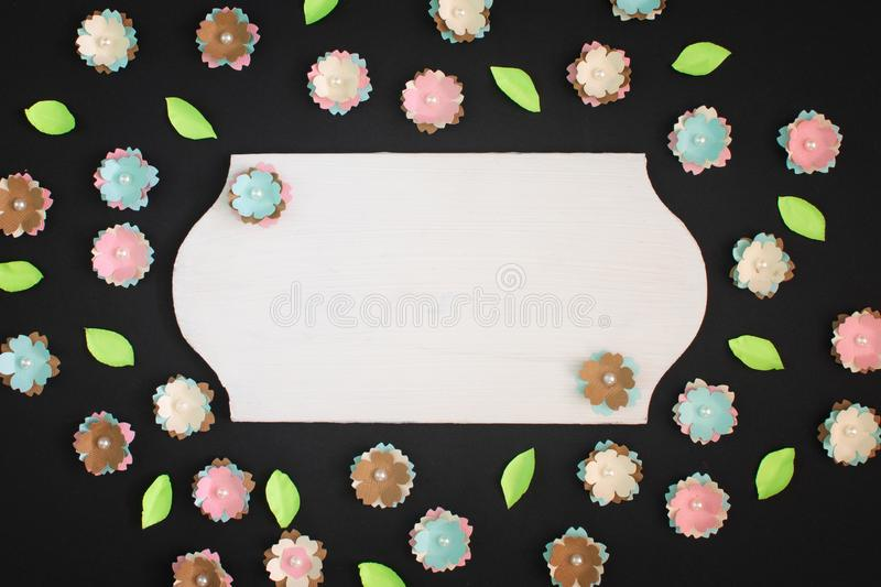 On a black background small flowers made of paper are randomly scattered. In the center is an empty plate with copy royalty free stock images
