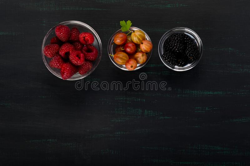 Black background with three plates of berries, raspberries and gooseberries stock photos