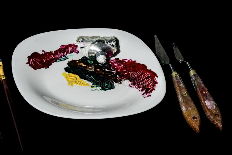 On a black background is a white porcelain plate. On the plate is a tube of paint and made color strokes. To the right of the stock photography