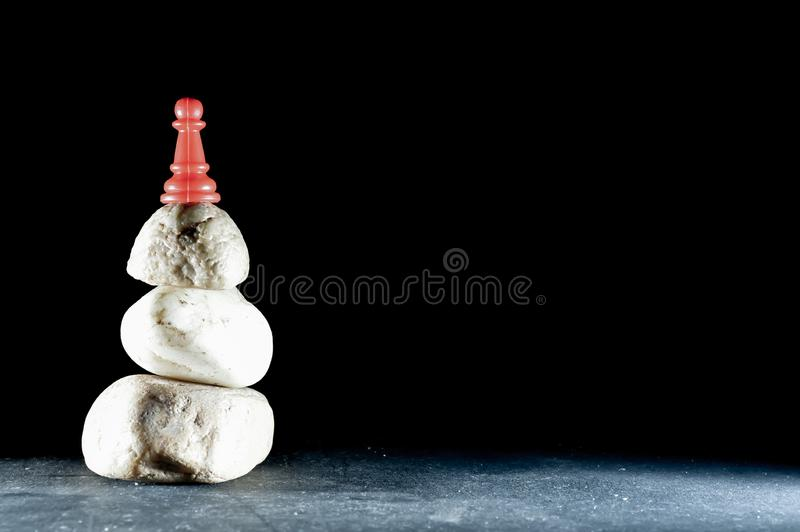 Black backgrouund top view and pawn on stone. Red pawn on stone and black backgrouund, player, promotion, winner, strategy, attack, silhouette, megalomaniac royalty free stock photo