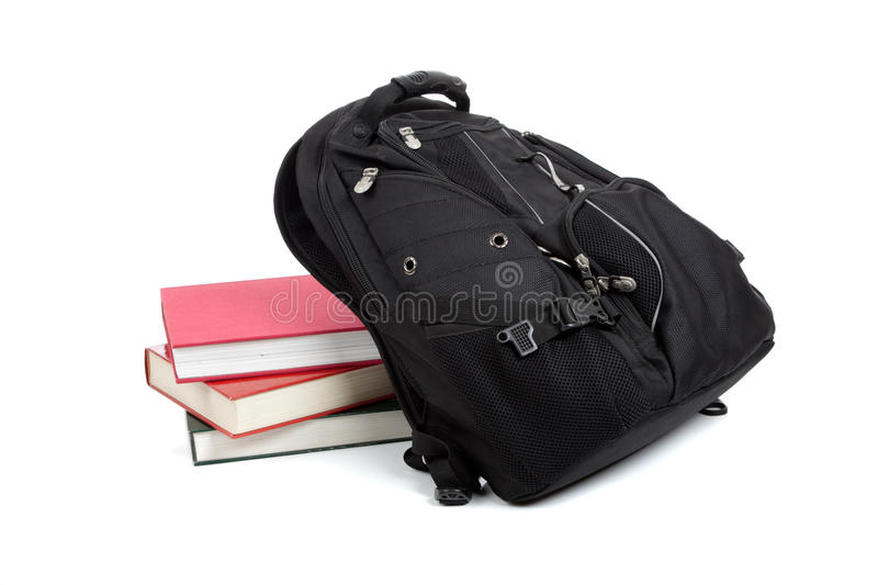 Black backpack with books on white stock images