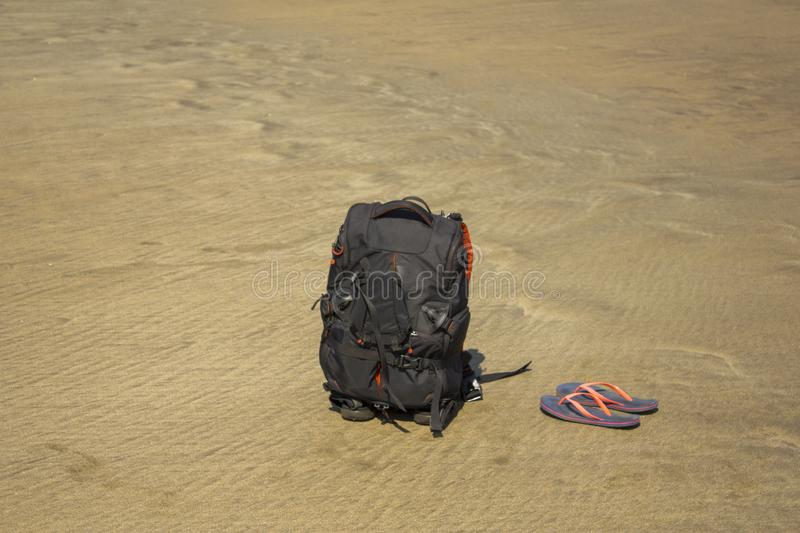 A black backpack and purple flip flops on the sand royalty free stock photography