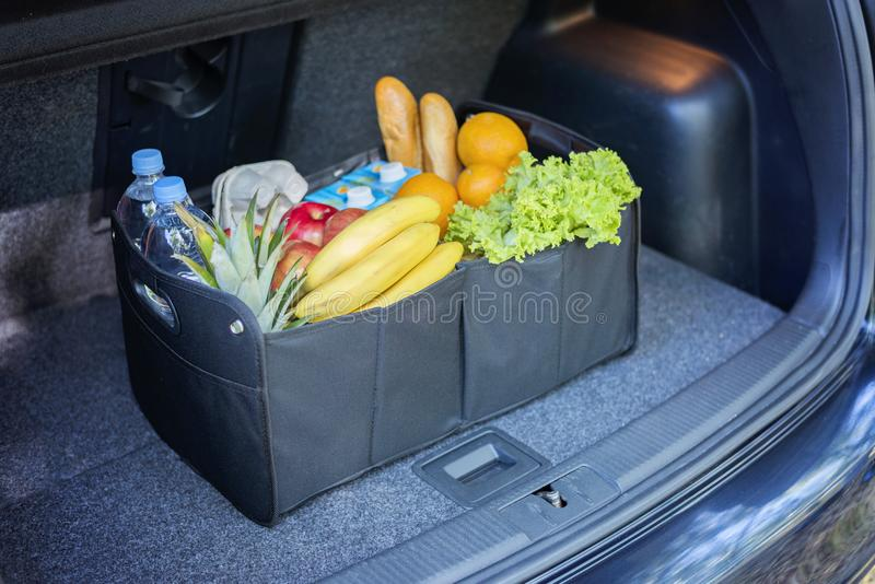 Black bag basket full of products in the car trunk royalty free stock photography