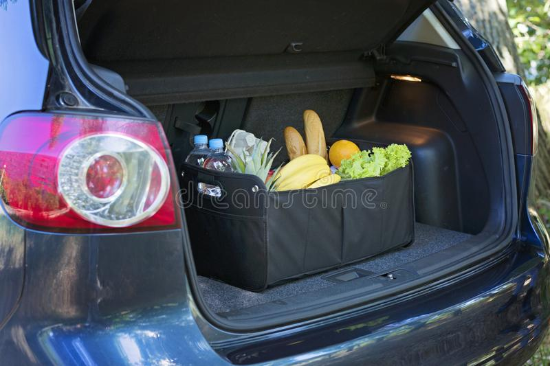 Black bag basket full of products in the car trunk royalty free stock image