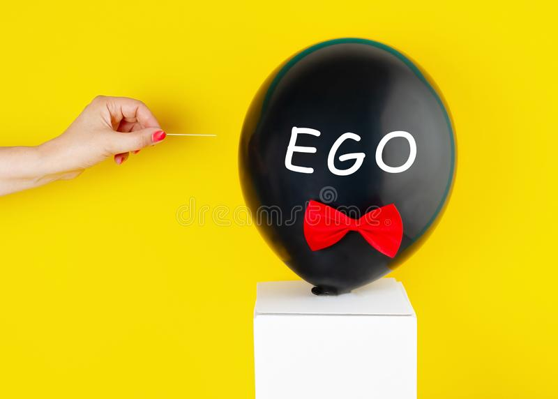 Black balloon with the text Ego over it and woman hand that is going to pop up balloon with needle. Ego destruction concept stock images