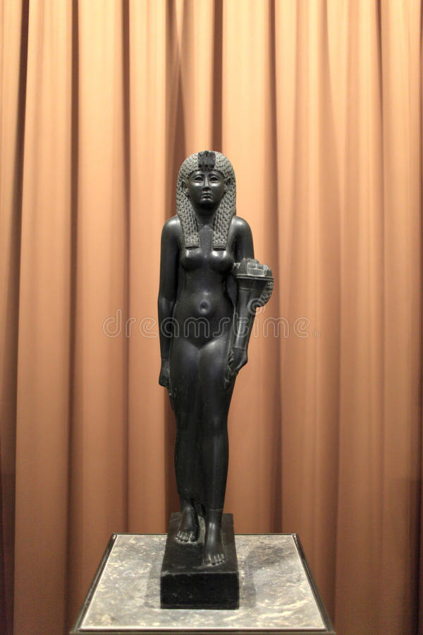 Black basalt statue of Cleopatra VII. On the brown background. She was the last person to rule Egypt as an Egyptian pharaoh royalty free stock photo