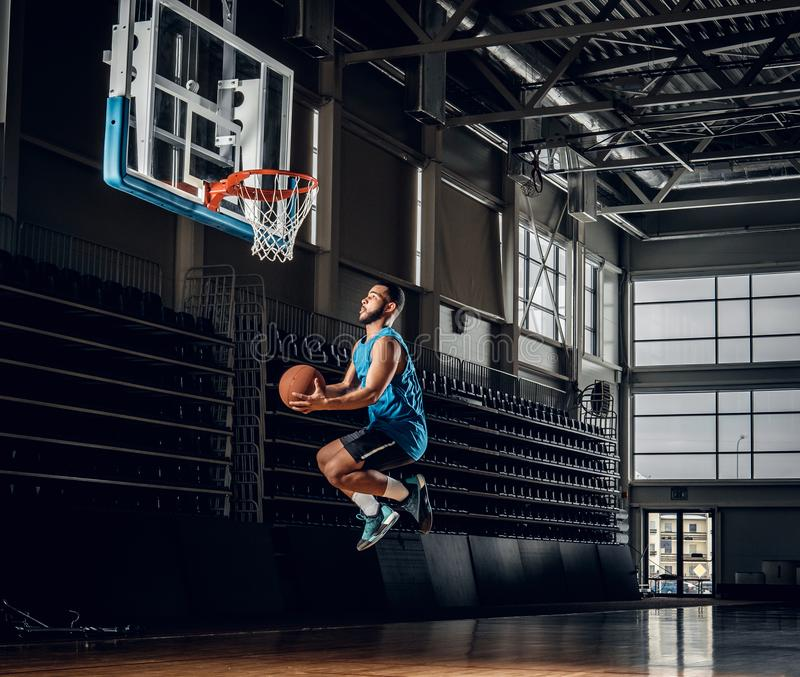 Black basketball player in action in a basketball court. royalty free stock photos