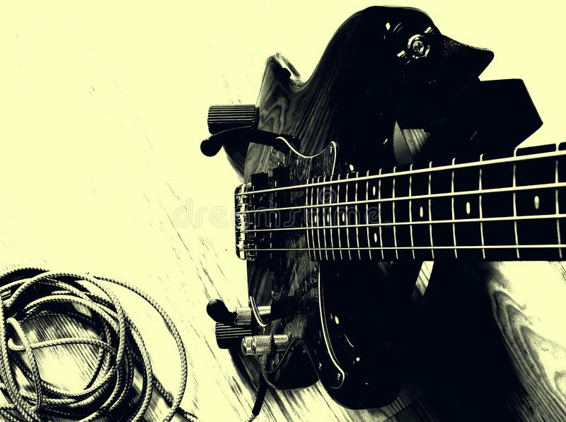 Black Bass guitar with guitar cable. Black bass guitar on stand with guitar cable from headstock music rock stock photo