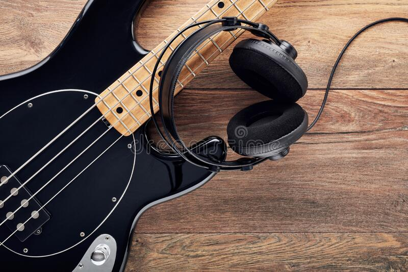 Black bass guitar with headphones on table. Black bass guitar with headphones on wooden table royalty free stock photo