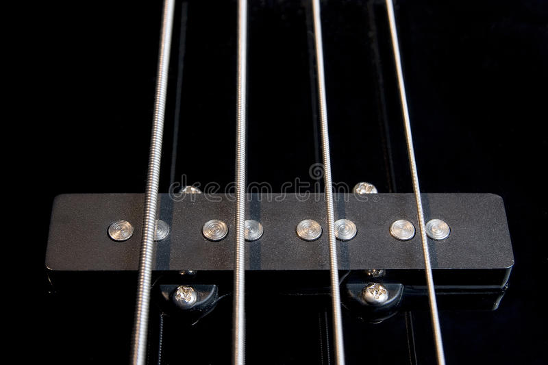 Black bass guitar pickup with strained strings stock images