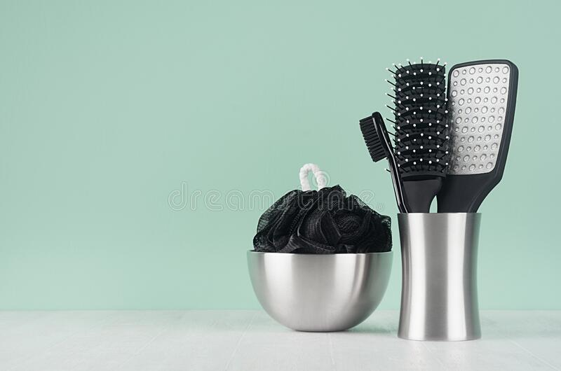 Black bathroom accessories in elegant green mint menthe interior on white wood table - bath sponge, brush, comb, toothbrush. Black bathroom accessories in royalty free stock images