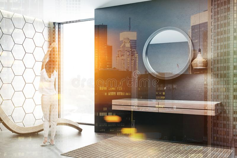 Black bathroom, double sink and armchair, woman. Woman in modern bathroom with black and gray honeycomb pattern walls and white double bathroom sink standing on royalty free stock images