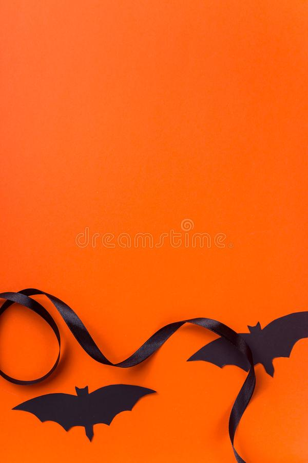 Black halloween characters and accessories on a bright orange background. Black bats and ribbon on an orange background as symbols and accessories for a stock photos