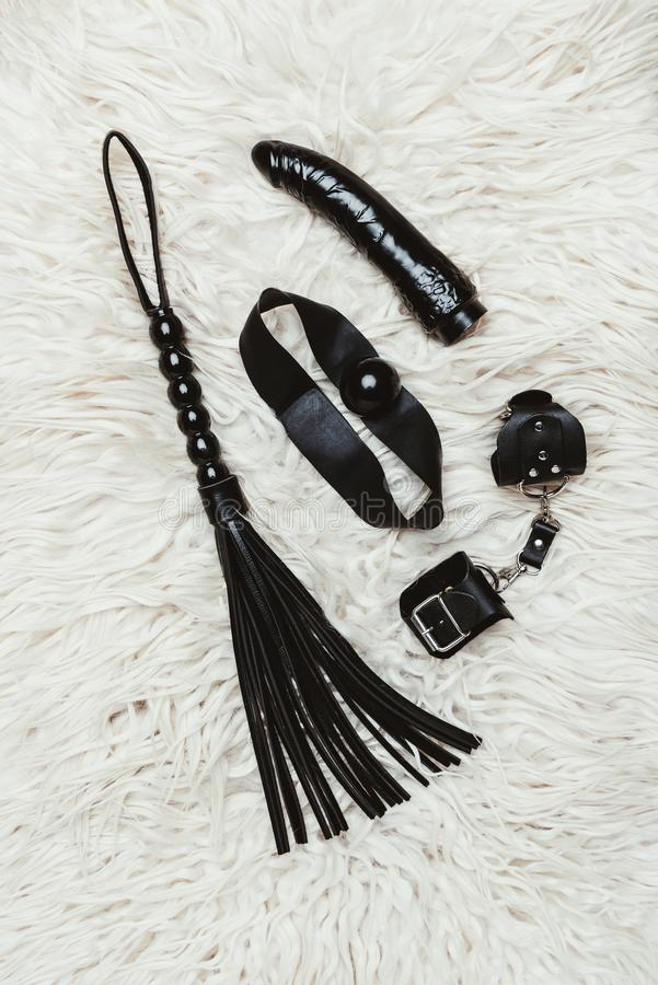 Black bdsm gag and vibrator with whip. On white carpet royalty free stock photos