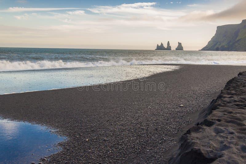 Black beach in background Dyrholaey - Vik, Iceland. Beauty dark sandy beach in background Dyrholaey stone - Vik, Iceland royalty free stock images