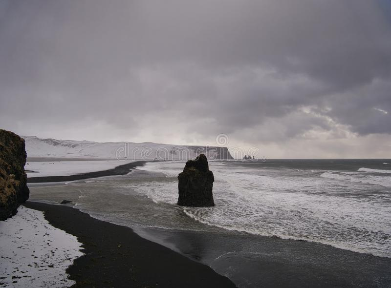 The Black Beach in Iceland with rocks in the sea. Photo from March stock photo
