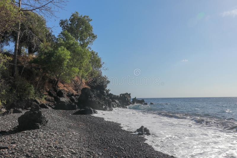 Black beach with lava pebbles and larger stone. Rock cliff of hardened volcanic lava. Slightly wavy sea, foamy water in the surf. stock photo