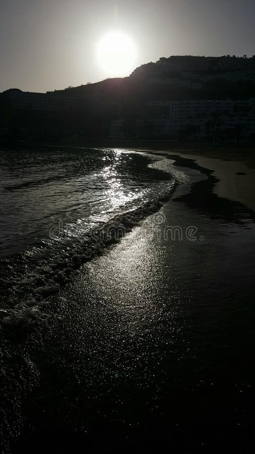 Black beach waves of the ocean tide at sunset reflects the sun. Sea, reflecting, ripples, gran, caneries, spain royalty free stock photography