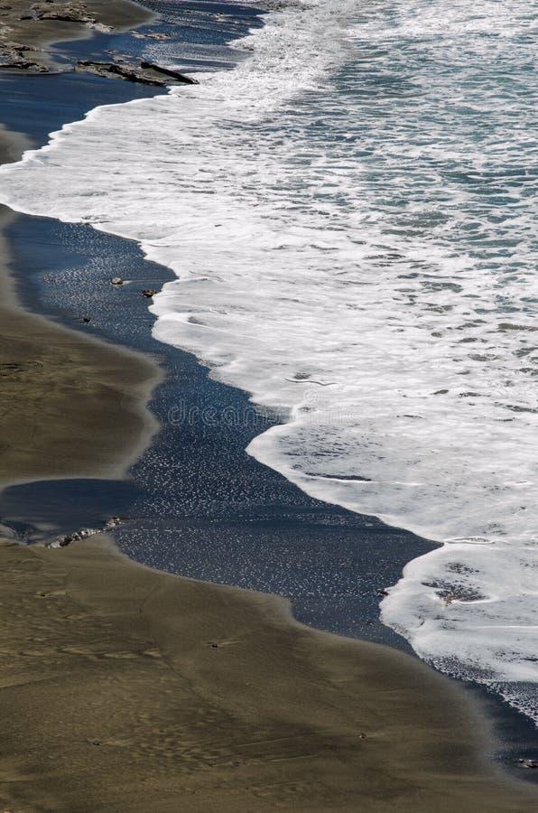 black beach and white wave stock photos