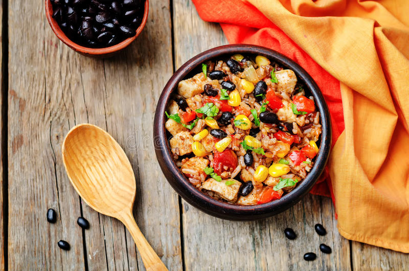 Black beans, corn and tomato red and white rice with chicken. Toning. selective focus stock photography
