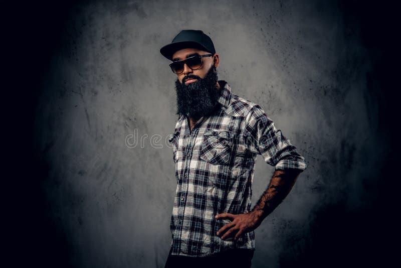 Black bearded male posing over grey background. stock photos