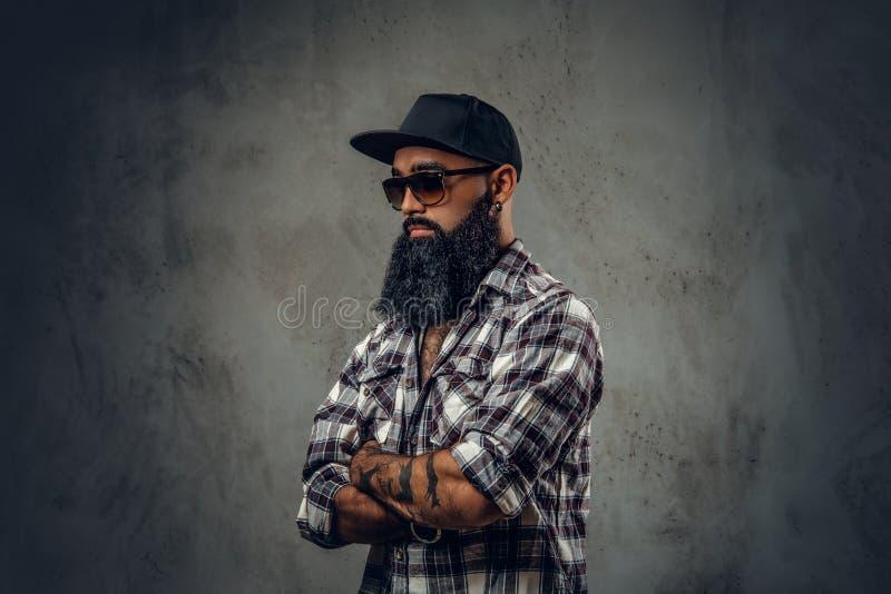 Black bearded male posing over grey background. stock image