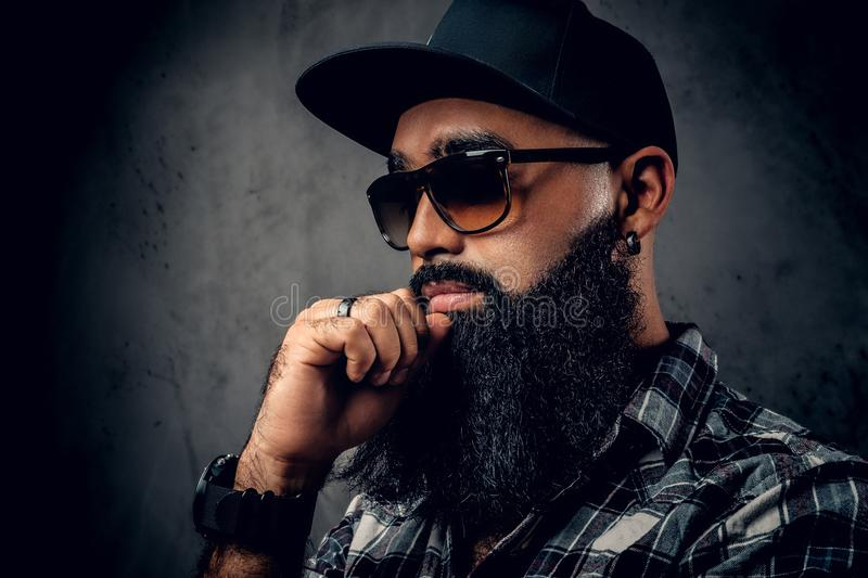 Black bearded male posing over grey background. stock images