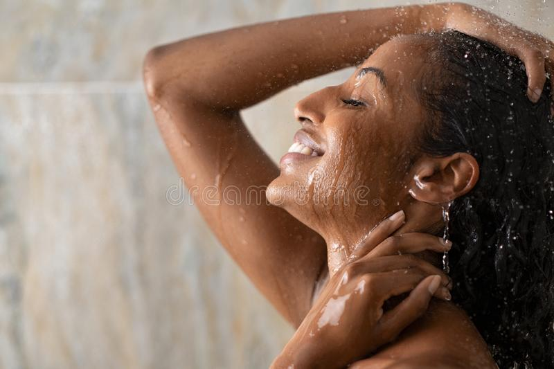 Black beautiful girl relaxing in the shower. Young woman taking a hot shower relaxing under warm running water. Smiling beautiful black woman enjoy during hot stock photography