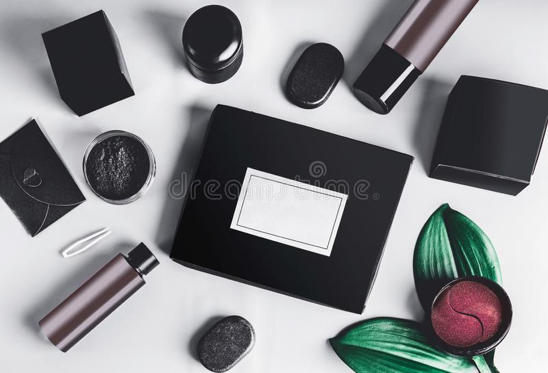 Black beauty box and various black and brown cosmetic product in jars and bottles with branding mock up. Eye patch. Snail mucin stock image