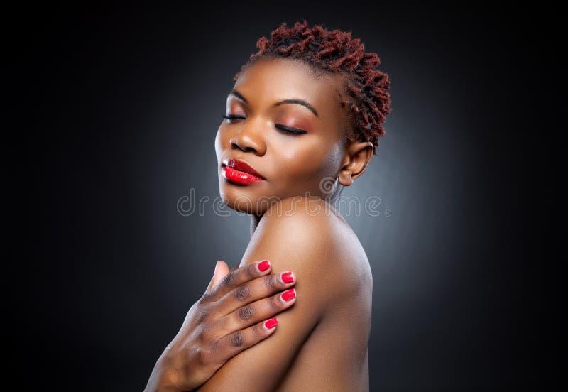 Black beauty with short spiky hair. Black beauty with short spiky red hair royalty free stock photo
