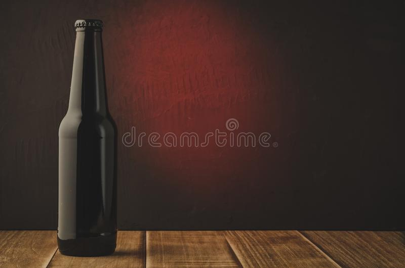 black beer bottle with red light background/ black beer bottle with red light background. Selective focus and copyspace royalty free stock photo