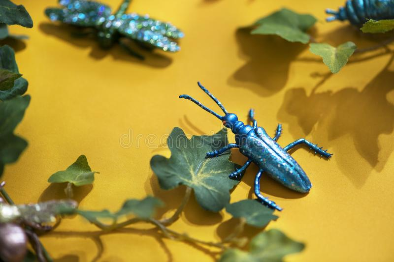 Black Beetle Decor on Yellow Surface With Green Leaves stock photos