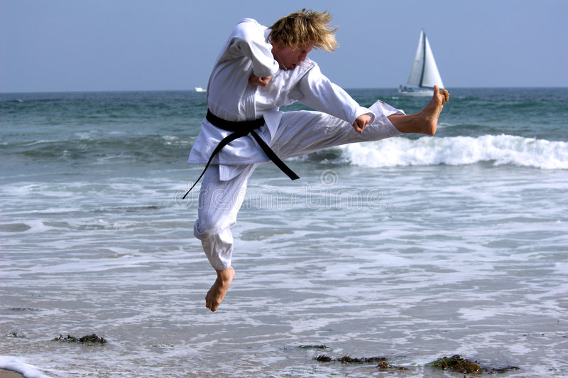 Black Belt Beach. Man with a black belt working out on the beach. Executing a flying kick royalty free stock photos