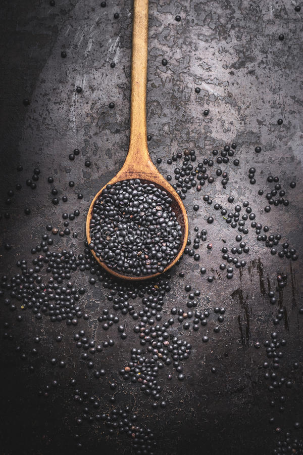 Download Black Beluga Lentil  Seeds In Wooden Cooking Spoon On Dark Rustic Background Stock Photo - Image: 83702020