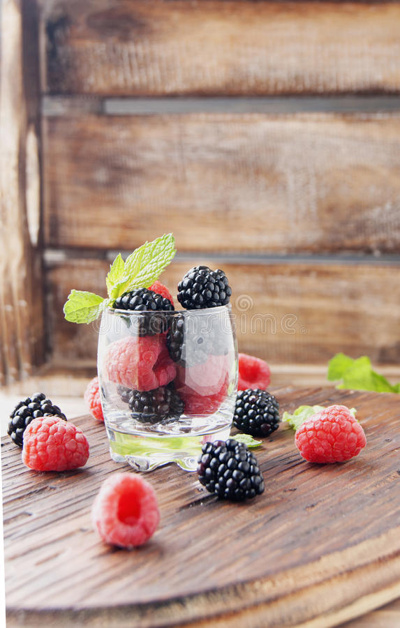 Black berries and raspberries in a glass cup royalty free stock photos