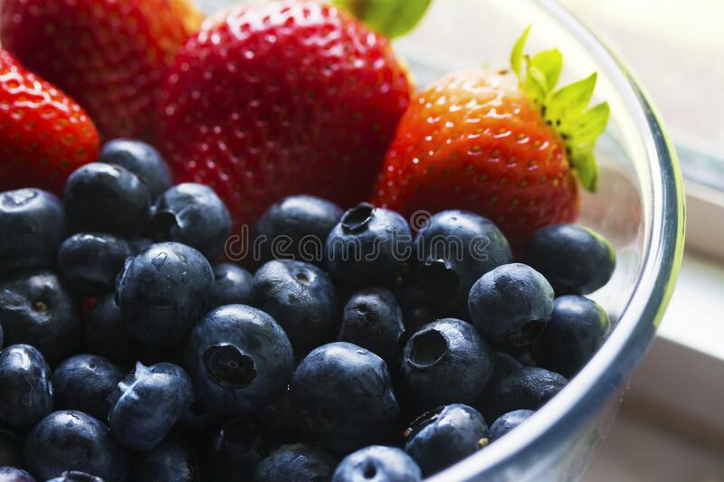 Black Berries Served Beside Strawberry on Clear Glass Bowl royalty free stock photos