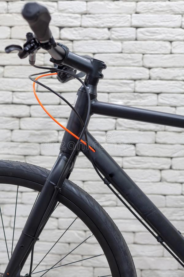 Black bicycle handlebar with speed switches, cables and brakes against a white brick wall. stock photos