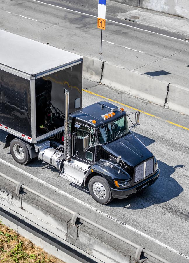 Black big rig day cab semi truck transporting black semi trailer driving on the interstate highway. Shiny Black professional industrial grade big rig day cab stock images
