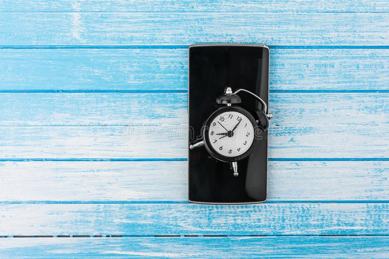 Black Big Screen Smart Phone With Reflection And Twin Bell Retro. Alarm Clock On It On High Contrast Blue And White Wood Background Top Angle royalty free stock photography