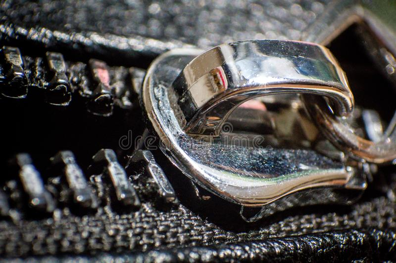 Black big zipper on leather material with shiny metal head in closeup photo royalty free stock photos