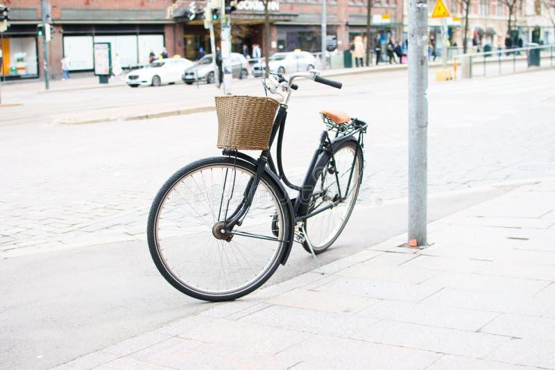 Black bike parked on the sidewalk. Black bike with a basket parked on the sidewalk on a city street royalty free stock photo