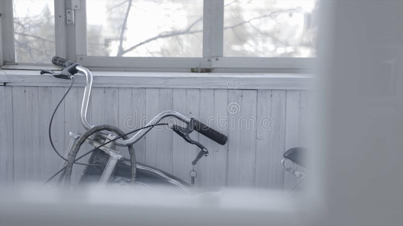 Black bike stands on grey wooden balcony. Action. High-speed old bike stands in closed clear balcony with windows and royalty free stock photos