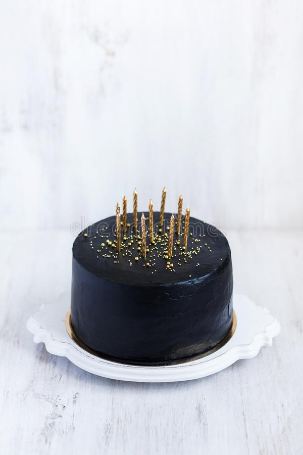 Black birthday cake with golden candles on white table. Black birthday cake with golden candles on white background stock images
