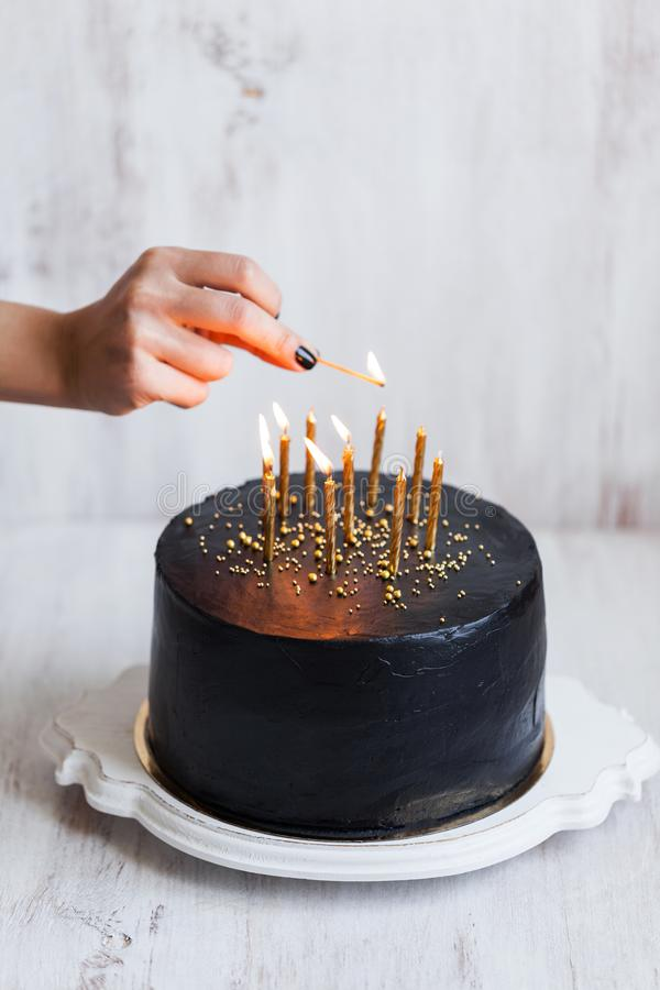 Woman hand burning candles on Black birthday cake. Black birthday cake with woman hand burning candles, white background royalty free stock image