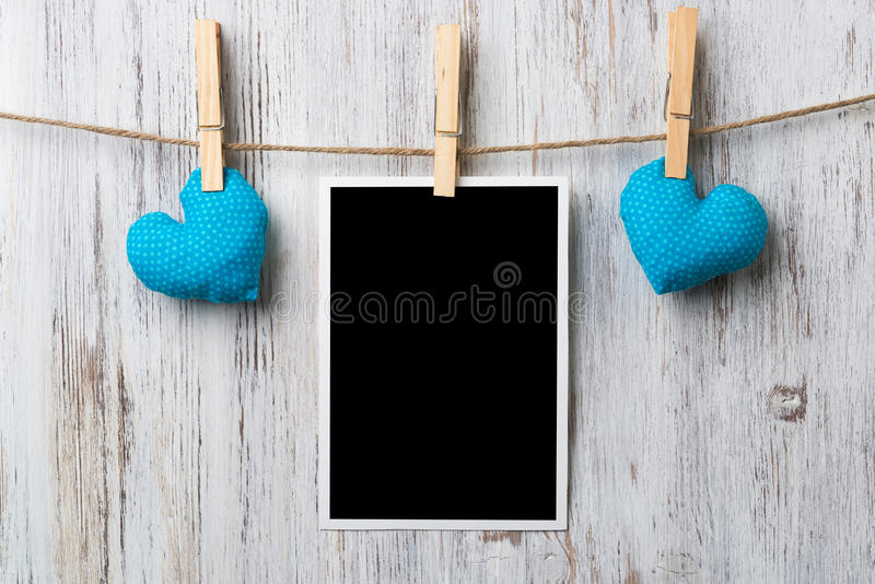 Black blank phote frame. Instant photo frame and love hearts pinned to rope on wooden textured background stock photography